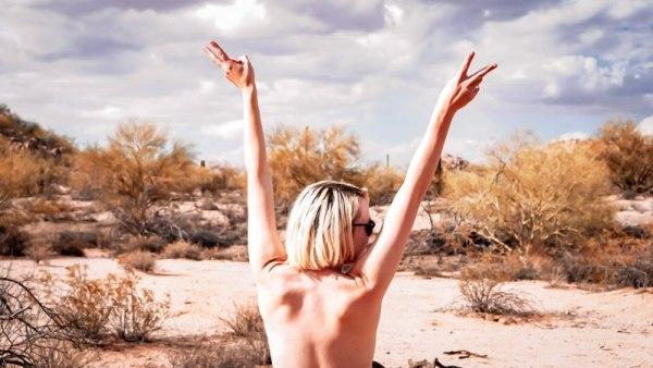 Kristen throws her hands up in the western US desert.