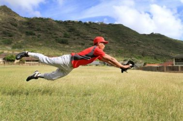 11562259 - baseball player dives to catch a stray ball