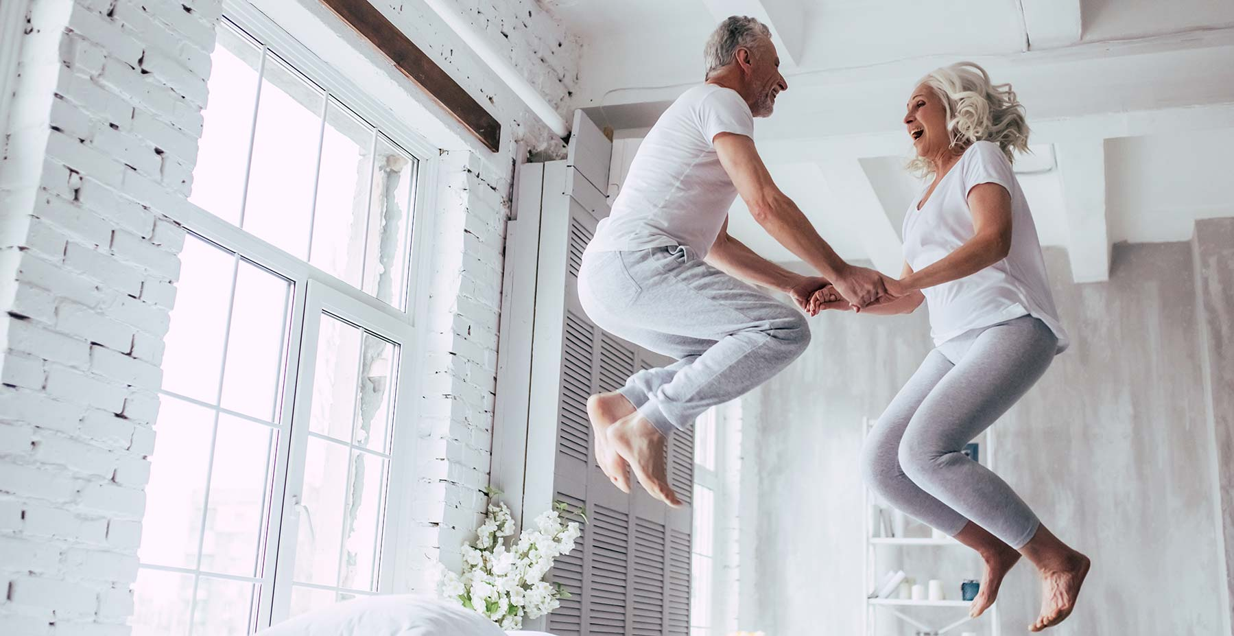 happy old couple jumping on bed