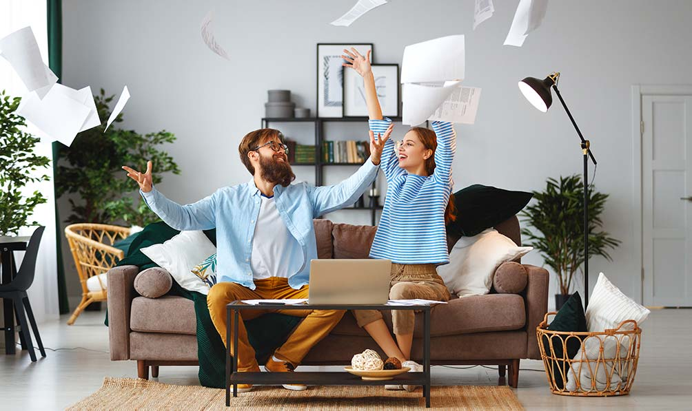 A happy couple throwing papers in the air after discovering mortgage refinance possibilities.