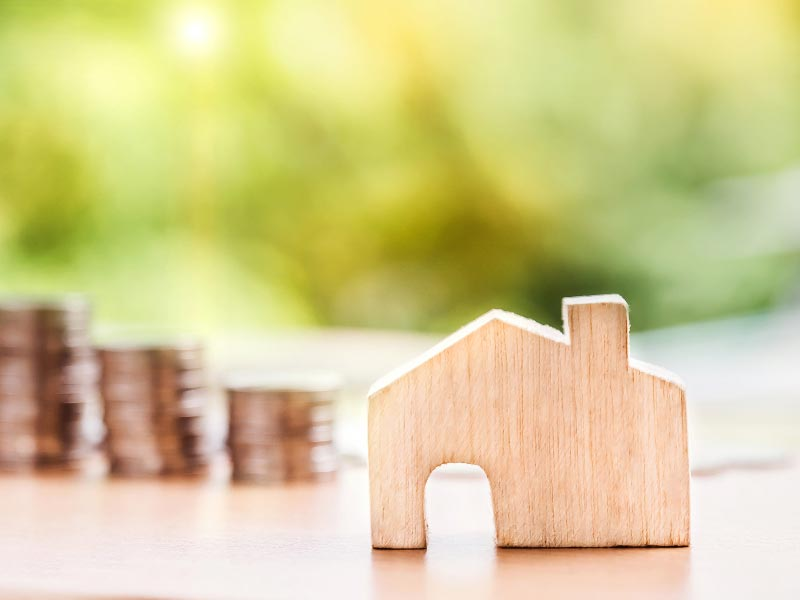 House and coins representing an investment property.