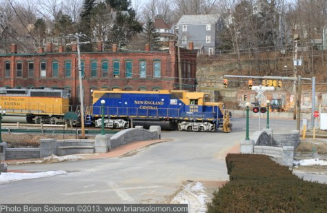 New England Central GP38 3850 leads train 608 at Stafford Springs on January 25, 2013. A series of difficult crossings in Stafford Springs is the primary reason for a 10 mph slow order through town. Especially difficult is this crossing, where the view of the tracks is blocked by a brick-building. Protection is offered by a combination of grade crossing flashers and traffic lights. Canon 7D with 40mm Pancake Lens; ISO 400 1/500th second at f8.0. In camera JPG modified with slight cropping to correct level and scaling for web. A RAW image was exposed simultaneously with the Jpg.