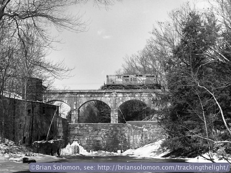 Boston & Maine GP9 1736 leads freight CVED southward across the stone arch bridge at Bernardston, Massachusetts on December 28, 1985. I exposed this using a Rollei Model T with a 'Superslide' insert that gave me a 645-size rectangle rather than a 2 1/4 inch square image.