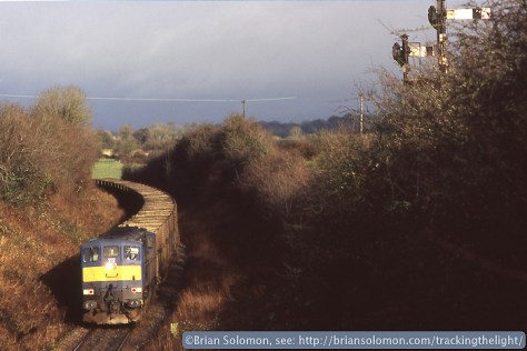 Northern Ireland Railways 112 is a General Motors diesel built to the specification of Irish Rail's 071 class. In 2003, it was on loan to Irish Rail and worked a great variety of trains. On the morning of November 29th, I made this view of it approaching Thomastown with an empty sugar beet train. The home signal was placed unusually high and setback from the line for sighting reasons.