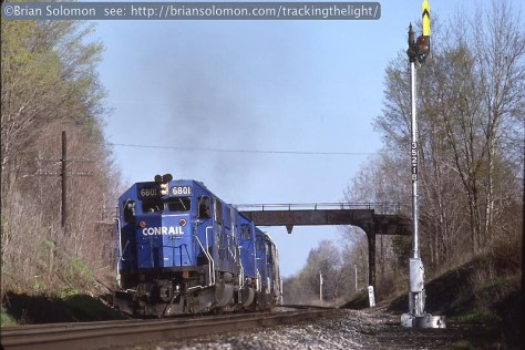 Caption: Conrail's former Erie mainlines in western New York state were protected by classic Union Swich & Signal Style S semaphores into the 1990s. Here, Conrail SD50s work the number 2 track with the eastward BUOI (Buffalo, New York to Oak Island, New Jersey) east of Dalton, New York on May 7, 1988. The signal protects the number 1 track (westward main track) Where Erie painted semaphore masts black, Conrail preferred an aluminum shade of silver. Exposed on professional Kodachrome 25 using a Leica M2 fitted with a visoflex and Leitz 200mm Telyt lens. Brian Solomon
