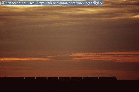 A Union Pacific coal train works east near Rochelle, Illinois. Exposed with a Nikon F3 on Fujichrome slide film. Notice the ditch-lights; I've given just enough of an angle so there's the faint twinkle at the front of the locomotive.