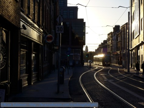 On October 4, 2014, an inbound LUAS tram approaches the intersection with Capel Street. I like the sunset  reflections on the tram and the sides of the buildings. By staying in the shadows, I minimize the effect of flare caused by bright light hitting the front lens element. Lumix LX7.