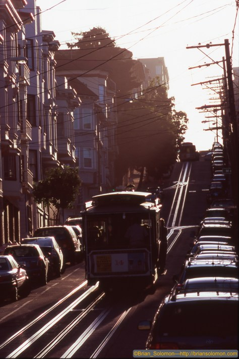 Cable cars ascend Nob Hill at sunset.