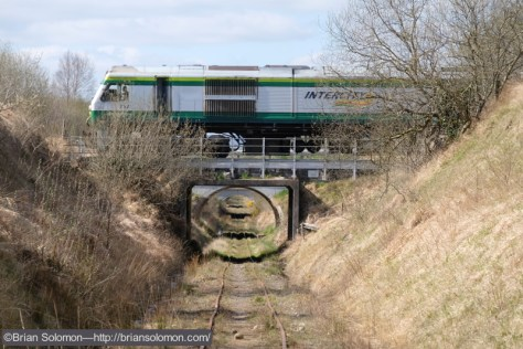 Cork-bound train with a 201-class  diesel crosses the Bord na Mona 3-foot gauge near Portlaoise. Fuji X-T1 photo.