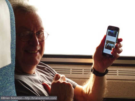 Richard J. Solomon checks Tracking the Light on his smart phone. Live from Amtrak 495! Lumix photo.