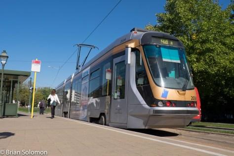 A STIB T2000 tram. in bright sun.
