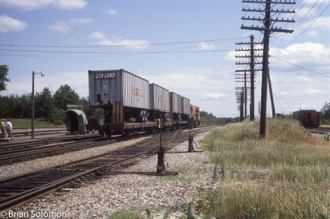 Maine Central's hot intermodal train East Wind blows through Northern Maine Junction in July 1983. Exposed on Ektachrome film with a Leica 3A with 50mm Summitar lens. Although not a great photo, this documented a fleeting period of railroading, and I'm glad to have made it.