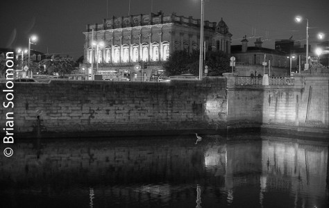 On a September 2016 evening, a lone heron stands in the River Liffey near Dublin's Heuston Station. Exposed on Ilford HP5 black & white film (rated at 400 ISO) and processed in Kodak HC110 (dilution B) for 4 minutes at 68 degrees (with a presoak water bath containing a hint of developer to help actuate initial development and improve shadow detail).