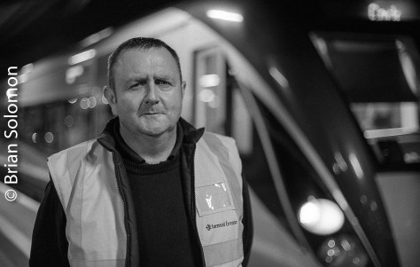 Cork-based Irish Rail train driver Ken Fox poses for a portrait with his InterCity Railcar at Dublin's Heuston Station. Exposed on Ilford HP5 using a Nikon F3 with Nikkor f1.8 50mm lens. Processed in Kodak HC110 (dilution D) and scanned with an Epson V500 flatbed scanner.