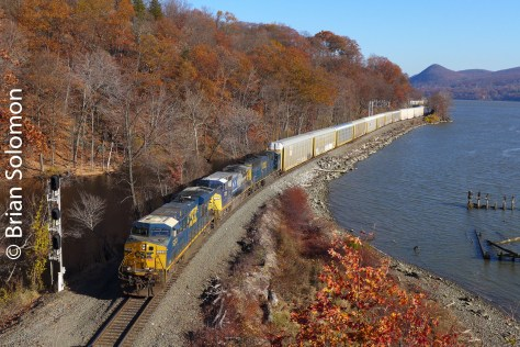 The train was moving relatively slowly, which allowed me to zoom out (to a wider focal length) as it approached. Which of the two views do you prefer? A southward CSX auto rack train hugs the Hudson at Mine Dock Park. Lumix LX7 photo.