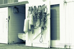 Monochrome nautical image of hanks of rope hanging on inside boats sheds on harbour edge with open door and dinghy stern in opening.