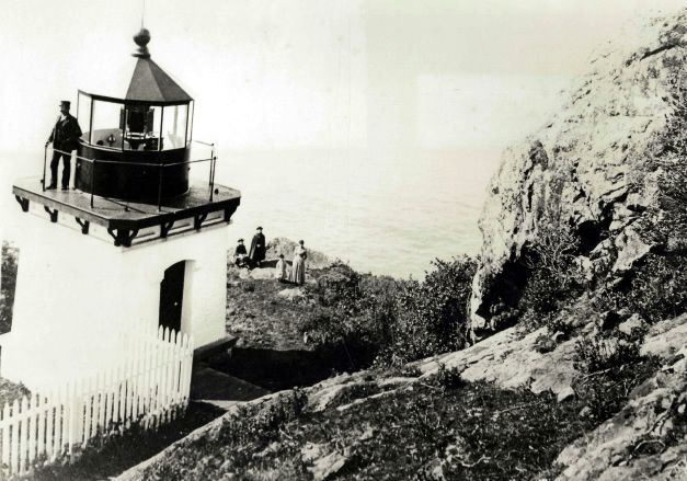 Captain Fred Harrington on lighthouse platform early 1900s. Below are his grandchildren, Ralph and Milton Hunter, Mrs. Harrington, and Maud Hunter. A.W. Ericson photograph copied by Katie Boyle 1966.
