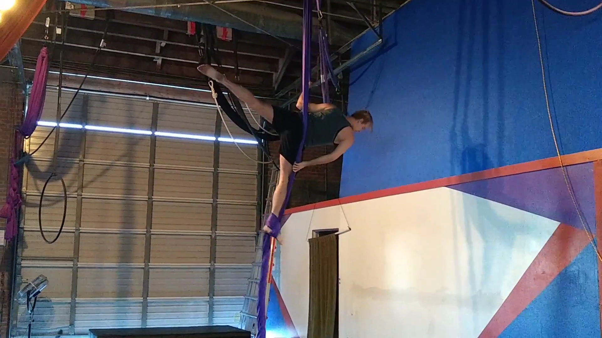 Snapshot of Brice LaGrand in an arabesque on the aerial silks.