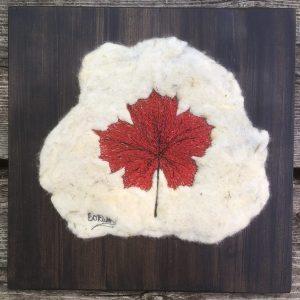 Thread painted red maple leaf on felt
