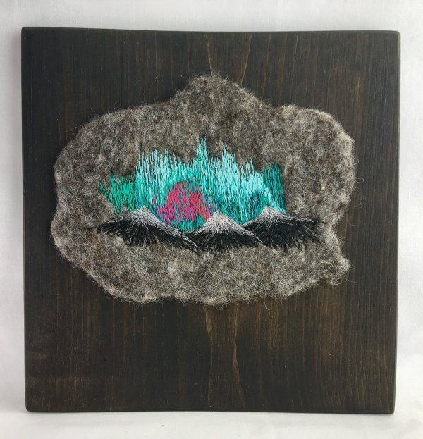 Northern Lights with mountains on felted fabric and mounted in wood