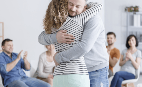 Picture of a couple hugging during group therapy, chair and people arranged in a circle