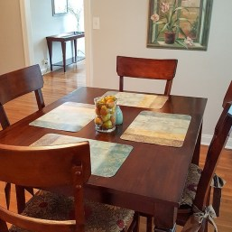 Photo of dinner table and chairs, hardwood floors, fruit, and artwork on the wall