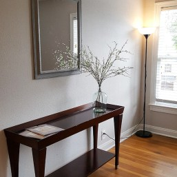 Entryway photo, table to put belongings, with vase and flower arrangement, hardwood floors, mirror and window