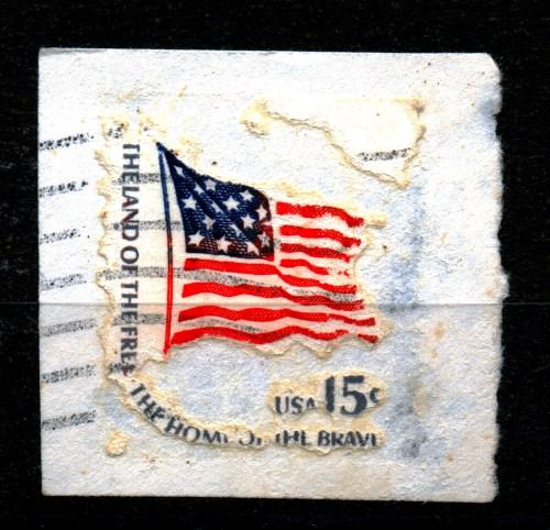 Zerfressene Briefmarke aus den USA auf Papier - ein kleines Kunstwerk. aber die Druckfarbe hat wohl nicht geschmeckt.