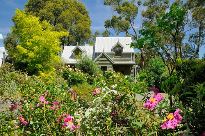 """All of our cottages are surrounded by lush gardens, lawns and trees. Many types of birds visit to feast on the abundant flowers, fruits and seeds. This photo shows one of our inter-connected Loft & Studio cottages (the Loft on the right and the Studio on the left). These """"storybook"""" designed cottages have wood fires, spas, air-conditioning, cathedral style ceilings and beautiful views of the grounds."""