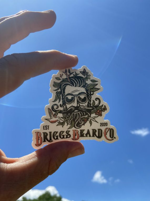 Briggs Beard Co. Sticker being held in front of the sky