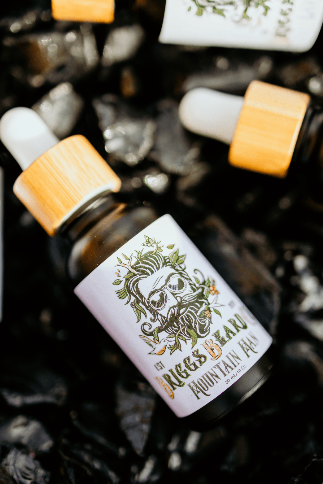 Mountain man beard oil lying in black stones