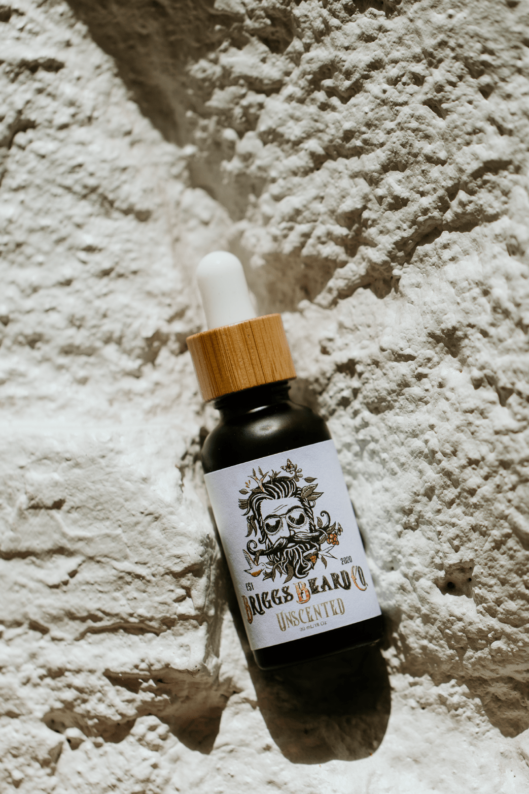 Vial of beard growth oil in a brick wall