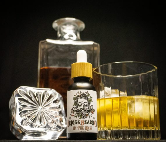 Briggs Beard Oil On the Rocks next to a whiskey glass and decanter