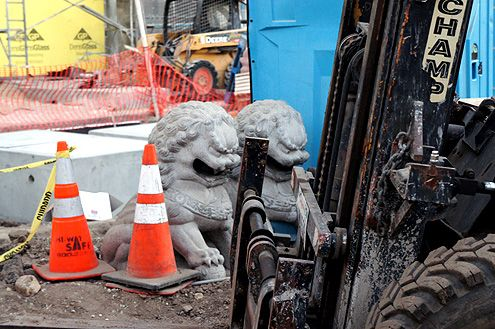 Twin lions that once guarded the previous building sit at the construction site that will guard the new center when completed