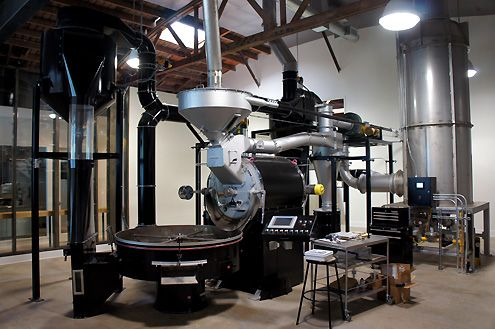 A large 60-kilo Probat coffee roaster visible to cafe patrons behind a large glass wall