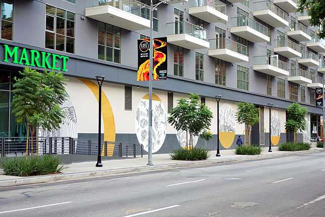 Mural by Italian artist 2501 adorns the wall along 8th Street