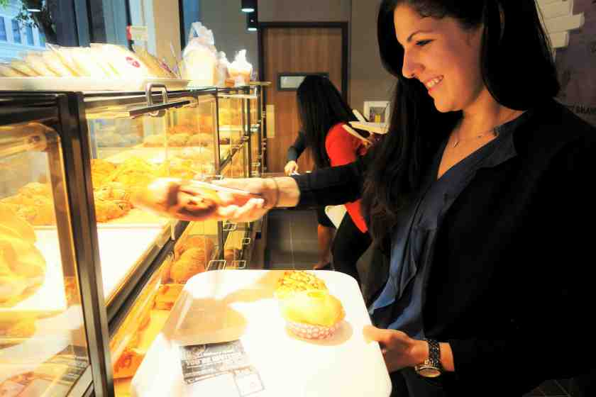 Customers grab a tray and tongs and choose from a wide variety of pastries