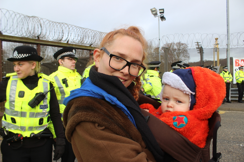 Mother and baby in front of police line.