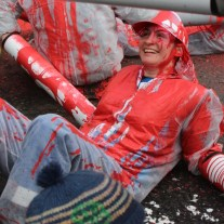 Cheerful protestor covered in red paint.
