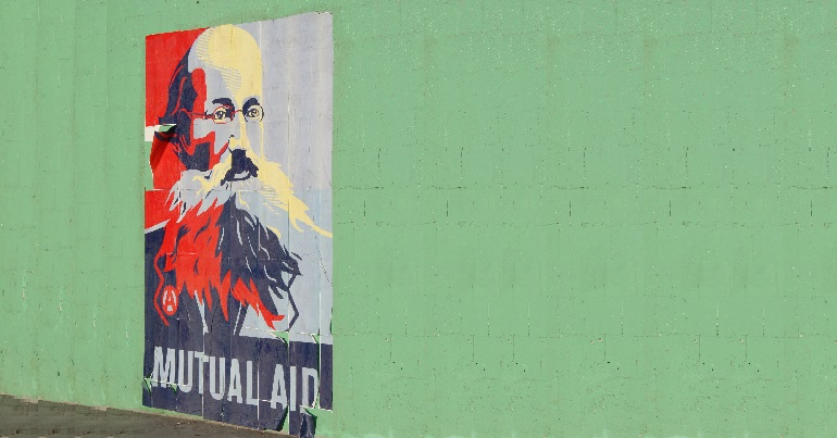 "Image of Kropotkin graffiti on a wall with the text ""mutual aid"""