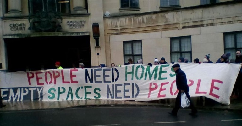 "Group of people holding a banner reading ""people need homes, empty spaces need people"""