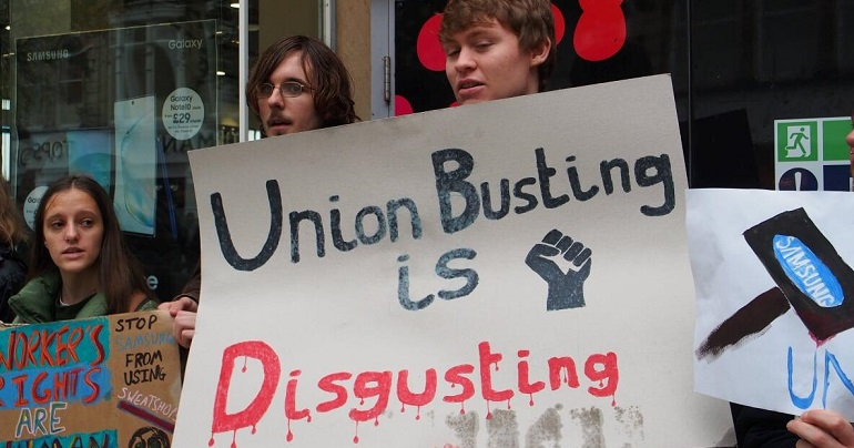 "A group of anti-sweatshop protesters with a sign reading ""union busting is disgusting"""