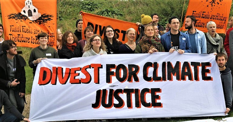 "A group of people holding a banner reading ""Divest for Climate Justice"""