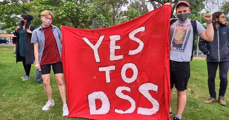 """A photo of Lucy Pegg and Chris Jarvis with a banner reading """"Yes to DSS"""""""