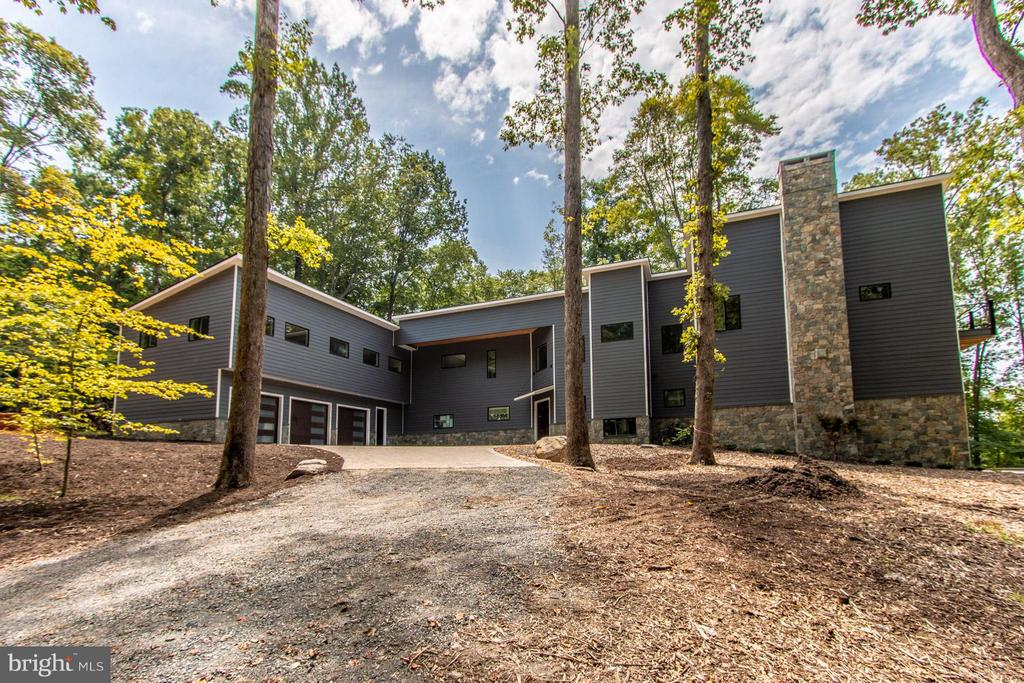 Spectacular one of a kind custom built  L shaped contemporary of hardy plank and stone with a 2 story exterior stone fireplace, paver driveway sitting on 5 private acres on 1000+ ft of the Occoquan River with views both north and south!  8000 sq ft 4/5 bedrooms, 5.55 baths, 3 levels facing west with scenic vistas from all the living space and 3 bedrooms! 3 car garage. Above the garage is a bedroom suite/inlaw suite/aupair suite w partial kitchen and full bath  as a wing to the gorgeous contermporary!  High ceiling ( 9.12.14 feet) and  open  floor plan!   Oversized double door solid wood entry to 2 story foyer. Elevator, deep coat closet, open offset metal staircase with wooden handrails to both the upper and lower level, plus second staircase! Huge full wall, floor to ceiling windows! 3 fireplaces- ll rec room, great room and master bedroom! Main level foyer entry, huge living room, separate dining room with  butlers pantry and deck access plus 2 half baths at either end. HUGE great room open to kitchen, island, customized cabinetry with quartz counter top luxury  SS appliances including subzero with front  window,  under the counter microwave, eurp styled double wall ovens, eurostyled gas downdraft  5 burner cook top, pocket handle dishwasher! Views from all room gorgeous but the great room overlooks the inground pool and the river! FIreplace and a wall of windows is breathtaking!Deck access from the great room with steps down to the pool! Upper level of main space has huge bedrooms, each with a balcony and a private ensuite bath! The master bedroom has a sitting area, fireplace, coffee bar, walk in closet and double closets, balony overlooking the river and the pool plus a glorious master bathroom with a separate soaking tub with scenic views, separate glass enclosed shower, private toliet and bidet toliet.  Gorgeous hardwood floors on two levels! Lower level features a stone fireplace, wall of windows with access to the  pool, plus an impressively organized utili