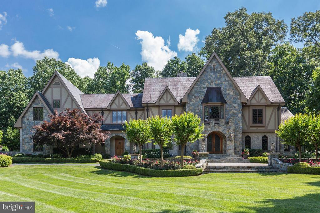 Truly magnificent, this stately English Tudor with old world architectural features including stone walls, stucco, aged brick, copper down spouts and slate roof create an impressive facade! Sited on almost 2 private, professionally landscaped acres w/ gated entrance & resort style amenities. Massive renovation done in 2008-2010. 4 finished LVLS that include English coffered ceilings, Italian mosaics, Brazilian mantel & American antique beams. The Foyer w/ Venetian twist columns opens to a 2-story Great Room that has coffered ceilings, masonry fireplace and French doors to the terrace and gracious paneled Library. The Living Room has beautiful arched windows and the banquet sized Dining Room has coffered ceiling and pocket doors. The Kitchen w/ exposed beams, custom cabinetry, two islands, top-of-the-line appliances designed for world class entertaining. There is also a cozy Breakfast Room with a masonry fireplace and bay window seating. The Upper Level has elegant Master Suite with a Sitting Room, luxurious Bath, custom walk-in Dressing Room and 3 spacious secondary Bedrooms. Additionally, there is an upstairs Family Room with a loft and two bedrooms. A sprawling Walk-out Lower Level includes a Recreation haven with Wet Bar, Custom Wine Cellar perfect for the connoisseur and an amazing Theater. An entertainer~s dream, the backyard with a spectacular setting includes a Pool, Private Spa surrounded by a stone wall, wood burning Fireplace, Pergola and gardens galore!