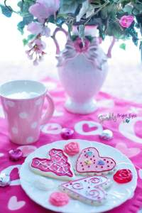 7 different ways to spoil your Valentine without flowers heart biscuits on plate, pink flowers in a fancy vase, pink mug with polka dots, hearts on tablecloth