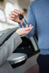 Woman receiving keys from a man in a car shop