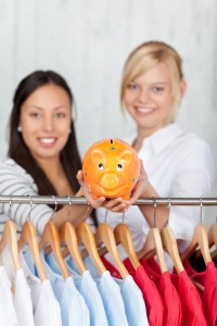 Women Holding Piggybank With Clothes Hanging On Rack At Shop