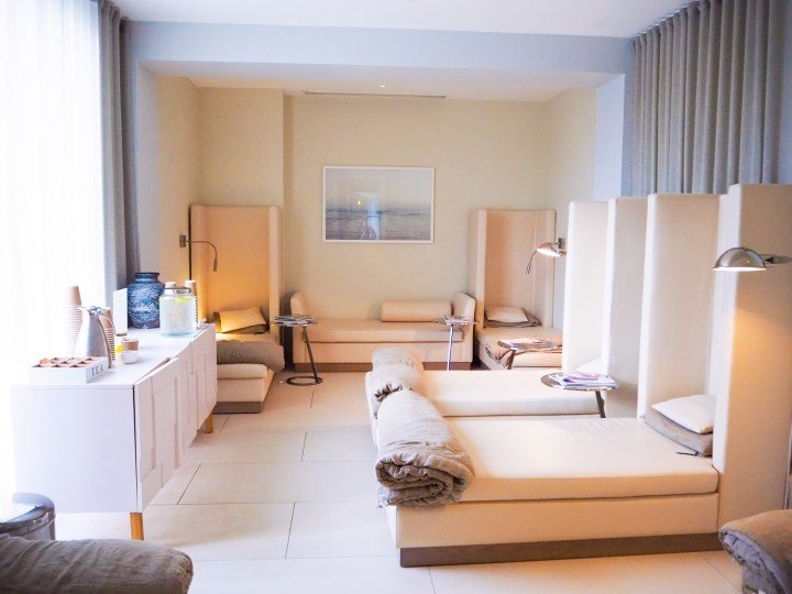 A relaxation room with a tea station, plenty of chaise lounges each with a lamp, pillow and duvet. The room is white and beige and very calming.